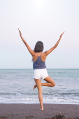 Young athlete woman practicing yoga on the beach