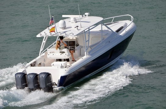 Blue and white sport fishing boat powered by three outboard engines