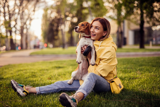 Woman and dog bonding in grass in park