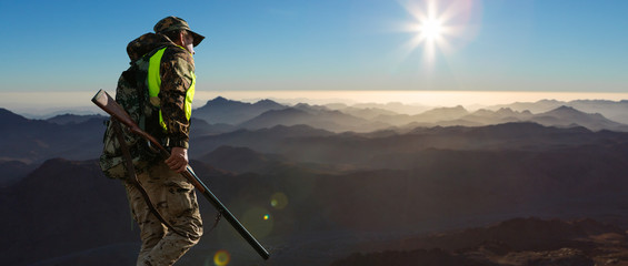 A hunter in camouflage and a gun in his hands in the early morning on top of a mountain stands looking for a target. Beautiful mountain landscape, the opening of the hunt.