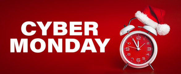 Red clock with Christmas Santa hat and Cyber Monday text. Time for Christmas shopping concept.