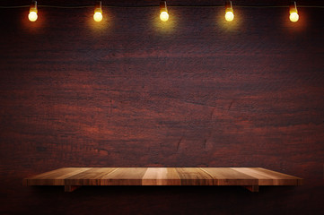 Empty brown plank wood shelf at black red wooden wall background with light bulbs string,Mockup for...
