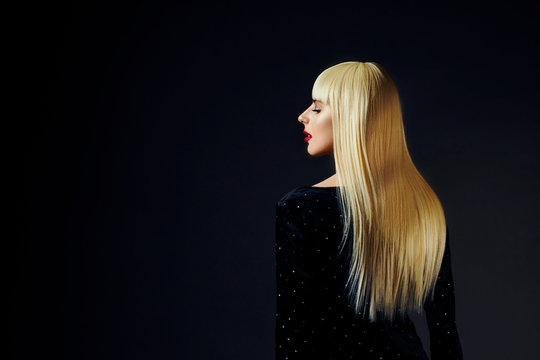 Profile portrait of a beautiful platinum blonde model with healthy, shiny  hair isolated on black studio background