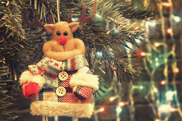 Toy deer on a Christmas tree on the background of Christmas lights