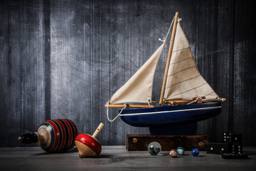 Wall Murals Ship Vintage toy still life with boat, tops, marbles and dominos
