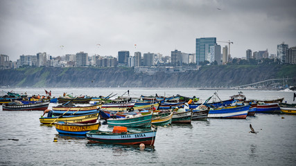 Lima, Peru - Nov 17, 2019: Fishing boats in Chorrilos harbour against the backdrop of the commerical Miraflores district