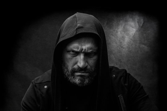 Black and white portrait of a bald bearded man in a hood on a dirty gray background