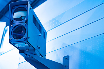 Two video cameras in one case. The cameras are mounted on the wall of the building. Access control to the enterprise. Security at the facility. The concept of video surveillance.