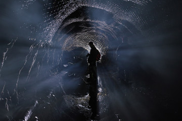 Silhouette of a man in an abandoned underground tunnel, an abstract image in a backlight. Abandoned mine.