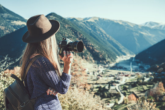 Stylish trendy hipster woman traveler photographer in a felt hat with dslr camera taking pictures of the mountains and uzungol lake in Trabzon during Turkey travel