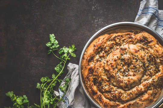 Turkish cuisine. Savory pie with Phyllo dough. Su boregi, burek or borek on dark rustic background. Top view.