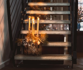 Cozy Christmas home decoration with four burning candles, cedar branches and snowflakes standing on the stairs at living room background. Happy holidays. Still life. Fourth advent. Indoor.