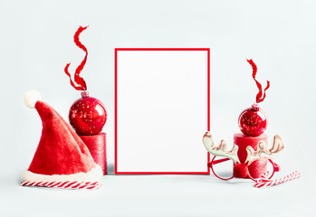 Christmas background with red decorations: Santa hat, baubles with ribbon and blank frame sign with Christmas tree stand on white background. Winter holidays . Copy space
