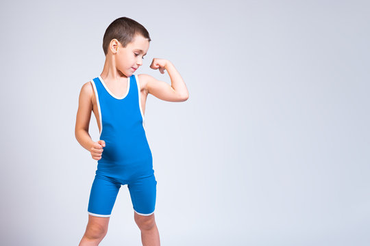 Portrait of a little cheerful boy in a blue  wrestling tights shows biceps, looks confidently at him and poses on a white isolated background. The concept of a little fighter athlete