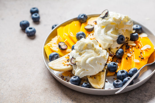 Healthy banana split with mango, chocolate and whipped cream on gray plate.