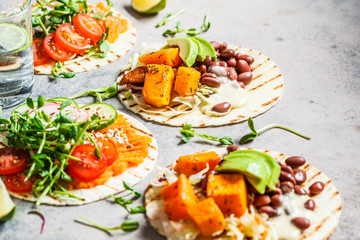 Open vegan tortilla wraps with sweet potato, beans, avocado, tomatoes, pumpkin and  sprouts on gray background, flat lay. Healthy vegan food concept.