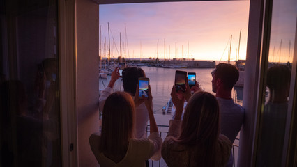 The young couples are making pictures with smartphones of panoramic view on a sea with yachts at sunset from a terrace of a hotel room during their summer vacation.