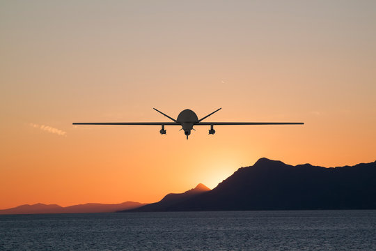 Silhouette of spy drone flying over the sea (UAV) and on the background beautiful view of sun hiding behind  surface of mountain
