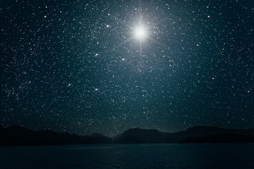 Wall Mural - sky against a bright night starry sky reflected in the sea
