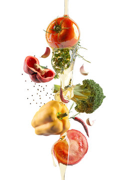 The flying colorful fresh vegetables and olive oil. Tomato, pepper, garlic and spices. White isolated background.