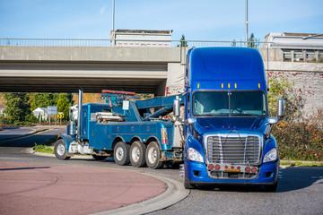 Big rig tow truck towing broken blue big rig semi truck tractor going under the bridge