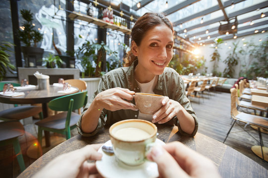Fisheye view of smiling woman holding coffee cup talking to friend across table in cafe, POV