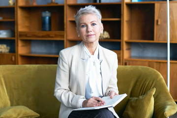 Attractive short haired middle aged female CEO sitting on comfortable couch in office interior writing in her notebook, checking appointment list, looking at camera with serious confident expression Wall mural