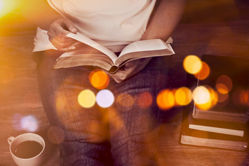 Close up of woman hands hold and reading bible indoor near a cup of coffee and book stack with...