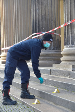 A policewoman checks for evidence outside the Green Vault city palace after a robery in Dresden