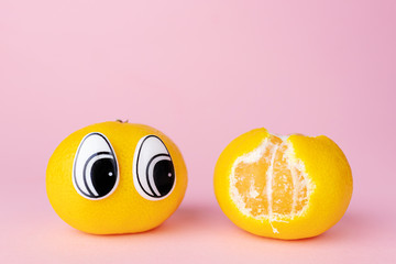 A mandarin with eyes looks at another mandarin with a partially peeled skin. Funny cute picture of fruits. Pastel pink background, place for text.
