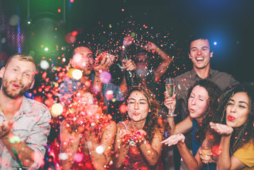 Happy friends doing party throwing confetti in nightclub - Group young people having fun celebrating new year holidays together in disco club - Youth culture entertainment lifestyle concept