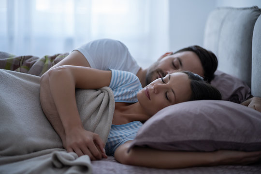 Young couple is lying in bed and sleeping.