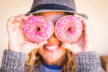 Nice cheerful middle age caucasian woman use a pair of sweet pink donuts like eyeglasses - funny image for diet and weight loss or breakfast concept