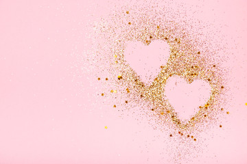 Two golden glitter hearts on a pink background
