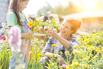 Smiling mother giving flowers to daughter while gardening at farm