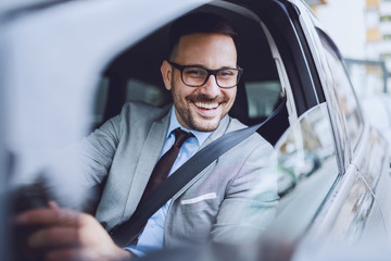 Cheerful caucasian businessman driving himself to work. Hands are on steering wheel.