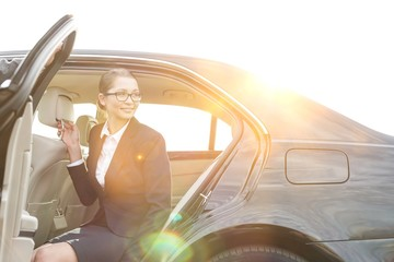 Cropped image of businessman holding car door for colleague against sky