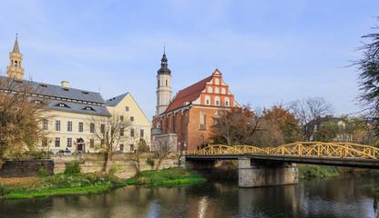 Kanał Młynówki w Opolu w okolicy Mostu Zamkowego, zwanego też Mostem Żółtym. Za mostem kościół pod wezwaniem Trójcy Świętej