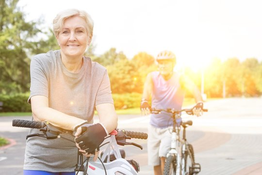 Confident senior woman leaning on bicycle in park
