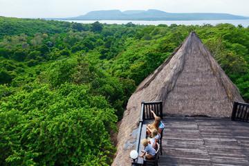 Aluminium Prints Dark grey Happy family travel, explore Menjangan rainforest near Pemuteran. Mother, kids relax on lounge veranda with tropical jungle view. Walking day tour, activity in adventure camp on Bali summer vacation.