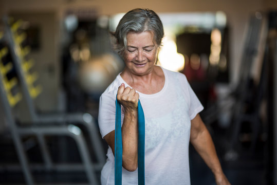 mature woman alone at the gym doing exercises with an elastic - healthy and fitness lifestyle and concept - senior or pensioner working her healthy