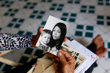 Nguyen Thi Dep looks at the old photos of her and baby daughter in Ho Chi Minh City