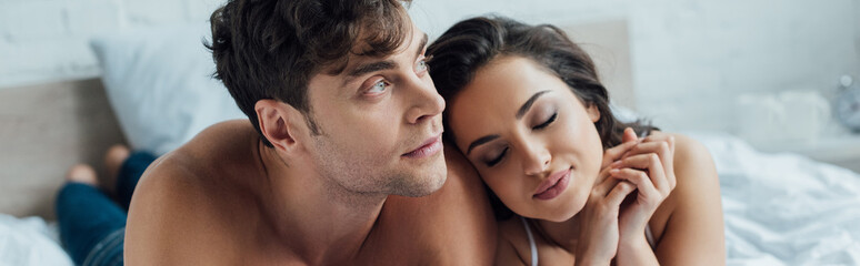 panoramic shot of dreamy man looking away while girlfriend with closed eyes leaning on his shoulder