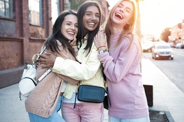 Outdoor shot of three young women having fun on city street