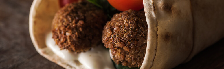 close up view of falafel with sauce and vegetables in pita, panoramic shot