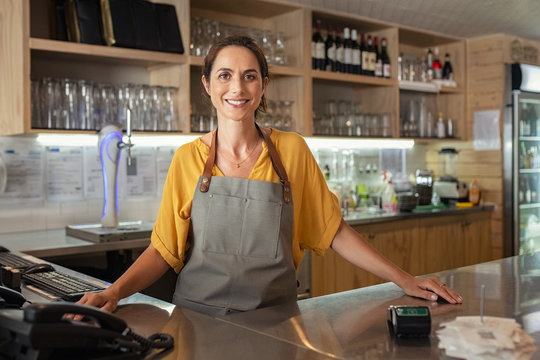 Proud waitress standing at counter