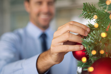 Business man decorating christmas tree at office