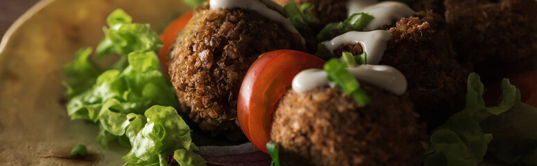 close up view of falafel with sauce on pita with vegetables in darkness, panoramic shot