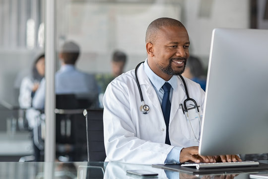 African mature doctor working on computer