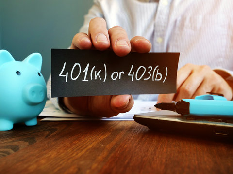 Hand is hilding 401k or 403b plan sign. Choosing retirement plan concept.